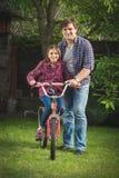 教他的女儿如何的愉快的年轻人被定调子的照片骑自行车 图库摄影