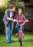 教他的女儿骑马成人自行车的年轻英俊的人在公园 库存图片