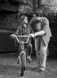 教他的女儿骑马自行车的年轻人黑白照片在公园 库存图片