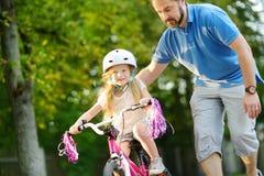 教他的小女儿的愉快的父亲骑自行车 学会的孩子骑自行车 库存照片