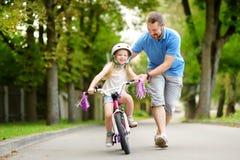 教他的小女儿的愉快的父亲骑自行车 学会的孩子骑自行车 库存图片