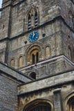 教会与蓝色时钟表盘的钟楼在经典样式在英国 免版税库存图片