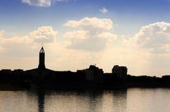 教会剪影在蓝天和在湖边 库存照片