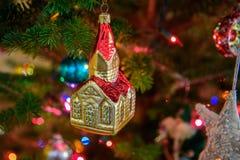 教会和尖顶的金和红色葡萄酒玻璃圣诞节装饰品 库存图片