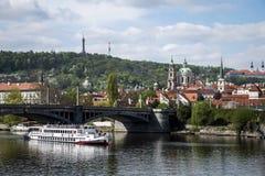 教会和桥梁的看法在伏尔塔瓦河河有小船的布拉格捷克 免版税库存图片