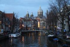 教会和运河在晚上在阿姆斯特丹,荷兰 免版税库存照片