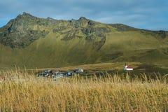 教会在有黄色花前景和山脉的小镇 库存照片
