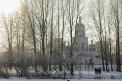 教会在从冻湖的冬天公园有人剪影的  免版税库存图片