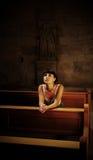 教会女孩祈祷的年轻人 免版税库存照片