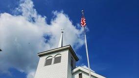 教会尖顶和美国国旗反对深蓝天 免版税图库摄影