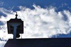 教会尖顶和钟楼剪影反对银色云彩 免版税库存照片