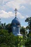 教会的闪耀的圆顶的美丽的景色有站立在绿色树中的一个被镀金的十字架的反对 图库摄影