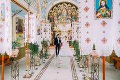 从教会走出去的新婚佳偶新娘和新郎握手 免版税库存图片