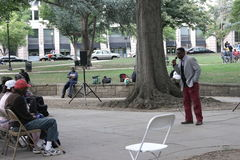 教会部长讲道对无家可归的人的和妇女在城市停放 免版税库存照片