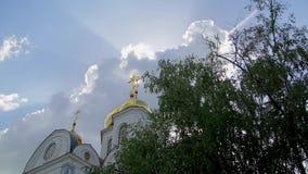 教会金黄圆顶有十字架和沙沙响的树叶子在背景天空 股票视频