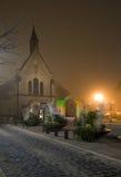 教会12月夜间雾照亮了老 免版税库存照片