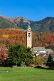 教区教堂和秋季山在背景 免版税库存图片