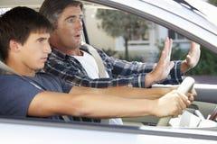 教十几岁的儿子的紧张的父亲驾驶 库存照片