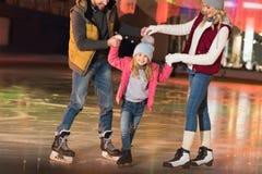 教可爱一点女儿滑冰的愉快的父母播种的射击  图库摄影