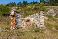 教堂和石墙的废墟在草甸,有树和草的 与蓝天的夏天天气 免版税库存照片