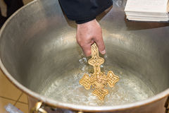 教士保佑洗礼仪式洗礼盘充满圣水在教会在仪式期间 免版税库存照片