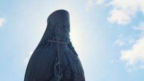 教士古铜色或石雕象特写镜头视图有十字架的在他的手上在反对蓝色多云天空的好日子 ?? 股票录像