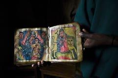 教士在埃塞俄比亚显示一本古老书 免版税库存照片