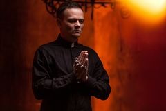 教士年轻宽容祈祷的教士画象在蜡烛旁边的祈祷用他的手 免版税库存图片