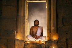 教士或信奉瑜伽者坐思考在疯狂古老华丽的小屋 免版税库存照片