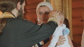 教士横渡婴孩,接触他的头;婴儿洗礼仪式 股票视频