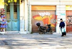 教士步行沿着向下街道在雅典,希腊 免版税库存图片