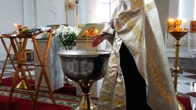 教士点燃灼烧的蜡烛用在字体的水洗礼仪式的  股票视频