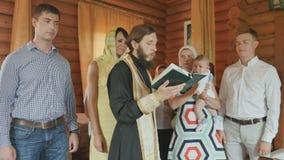 教士读一个祷告,父母,并且名义双亲听;婴儿洗礼仪式 影视素材