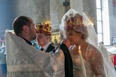 教士给酒一个被加冠的新娘 免版税图库摄影