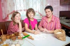 教她两个女儿的妈妈烹调在厨房 图库摄影