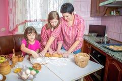 教她两个女儿的妈妈烹调在厨房 免版税图库摄影