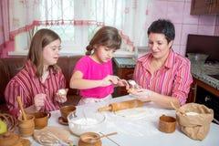 教她两个女儿的妈妈烹调在厨房 免版税库存图片