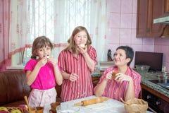 教她两个女儿的妈妈烹调在厨房 库存照片