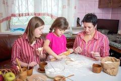 教她两个女儿的妈妈烹调在厨房 免版税库存照片