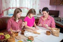 教她两个女儿的妈妈烹调在厨房 库存图片