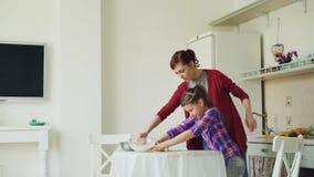 教她小的逗人喜爱的女儿辗压面团的年轻母亲,当在家一起烹调在厨房里在度假时 影视素材