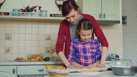 教她小的逗人喜爱的女儿辗压面团的愉快的母亲,当在家一起烹调在厨房里在度假时 股票录像