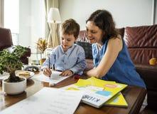 教她的儿子的妈妈做家庭作业 免版税库存照片