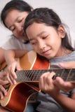 教她的女儿的妈妈弹吉他 免版税库存照片
