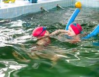 教她的妹的女孩游泳在水池 免版税图库摄影