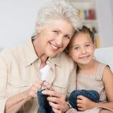 教她的孙女的祖母编织 图库摄影