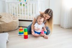 教她的小儿子的美丽的年轻母亲使用与玩具 库存照片