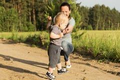 教她的小男婴儿子第一独立步的美丽的母亲 库存照片