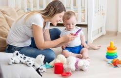 教她的男婴如何的愉快的微笑的母亲使用手机 免版税库存照片