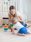 教她的男婴怎么的美丽的妇女画象对assembl 免版税库存照片